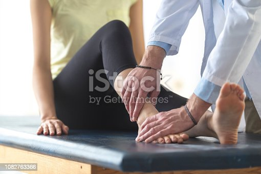 A woman is sitting on an examination table in a doctor's office. She has her shoes and socks off and the doctor is examining one of her ankles.