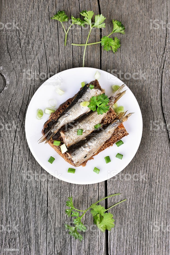 Sprats sandwich with herbs on rustic table stock photo