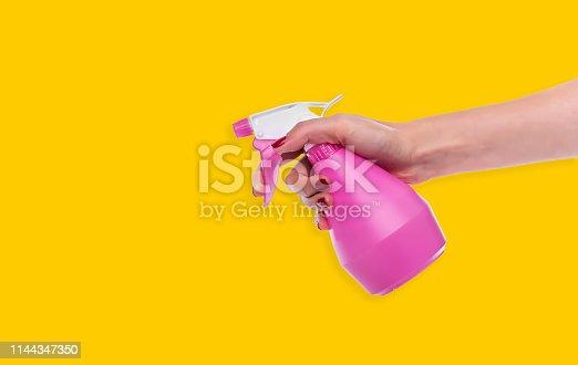 istock Spray bottle in female hand on yellow background. 1144347350
