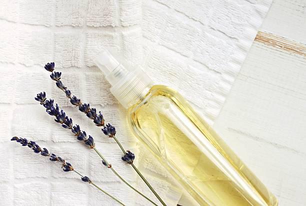 spray bottle of oil on towel with lavender - spruzzo profumo foto e immagini stock