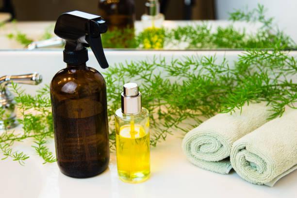 spray bottles, towels and greens on bathroom countertop - fresh start yellow stockfoto's en -beelden