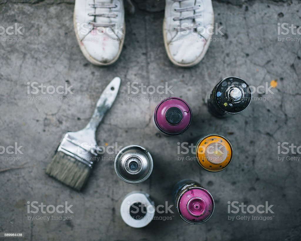 Spray cans and brush on sidewalk stock photo