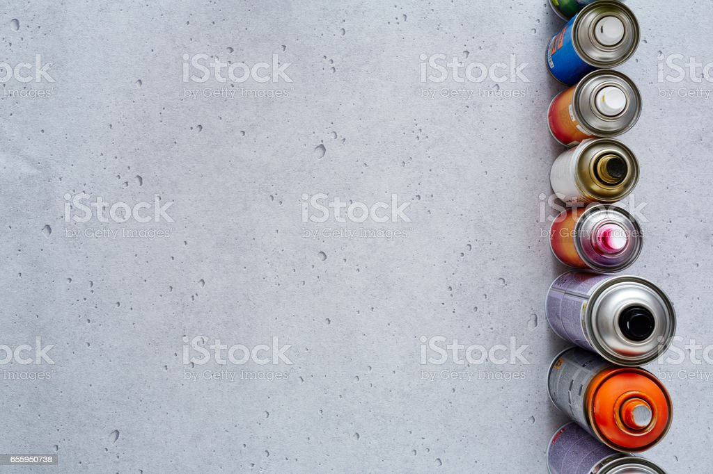 spray cans in lined up on concrete stock photo