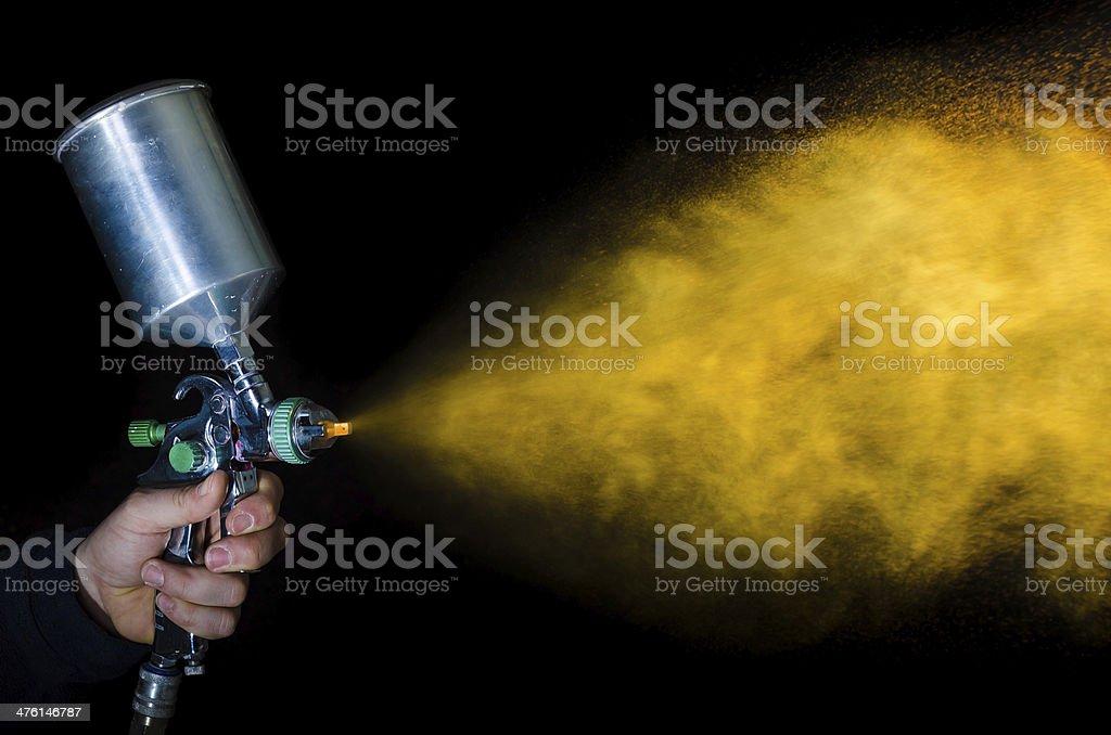 Spray gun in hand on dark background stock photo