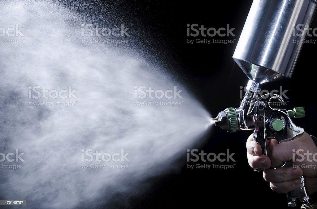 Spray gun in hand on dark background stock photo