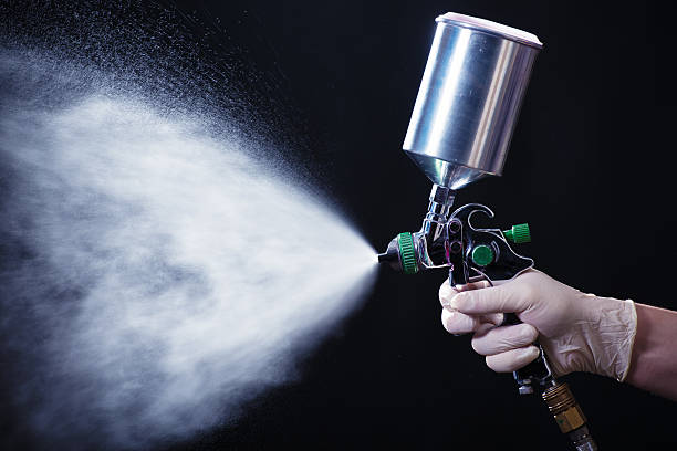 Spray gun in hand stock photo