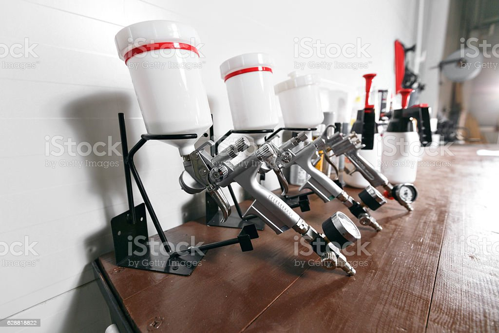 spray gun on wood table. in auto service. used for stock photo