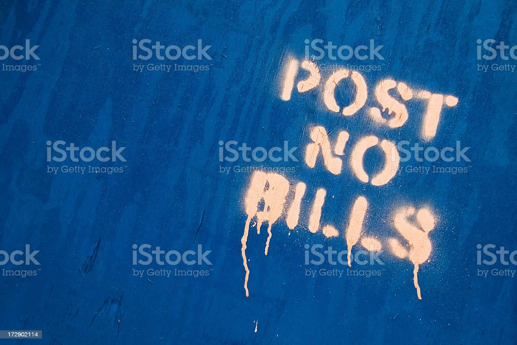 Spray paint on blue plywood states: 'Post No Bills'. royalty-free stock photo