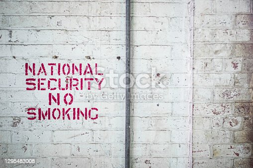 A spray painted stencil sign saying 'National Security No Smoking' in bright red on a white brick wall in an abandoned factory and industrial complex