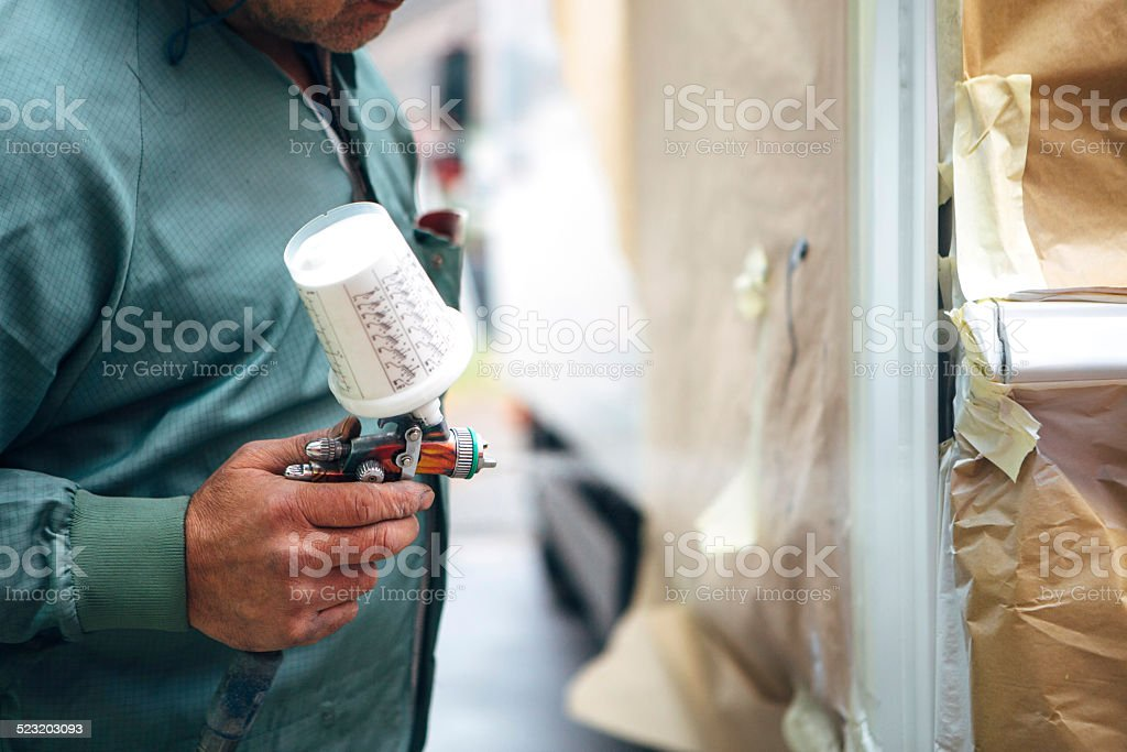 Spray Painter in coveralls spray a part of a car mechanic in coveralls spray a part of a transporter Adult Stock Photo
