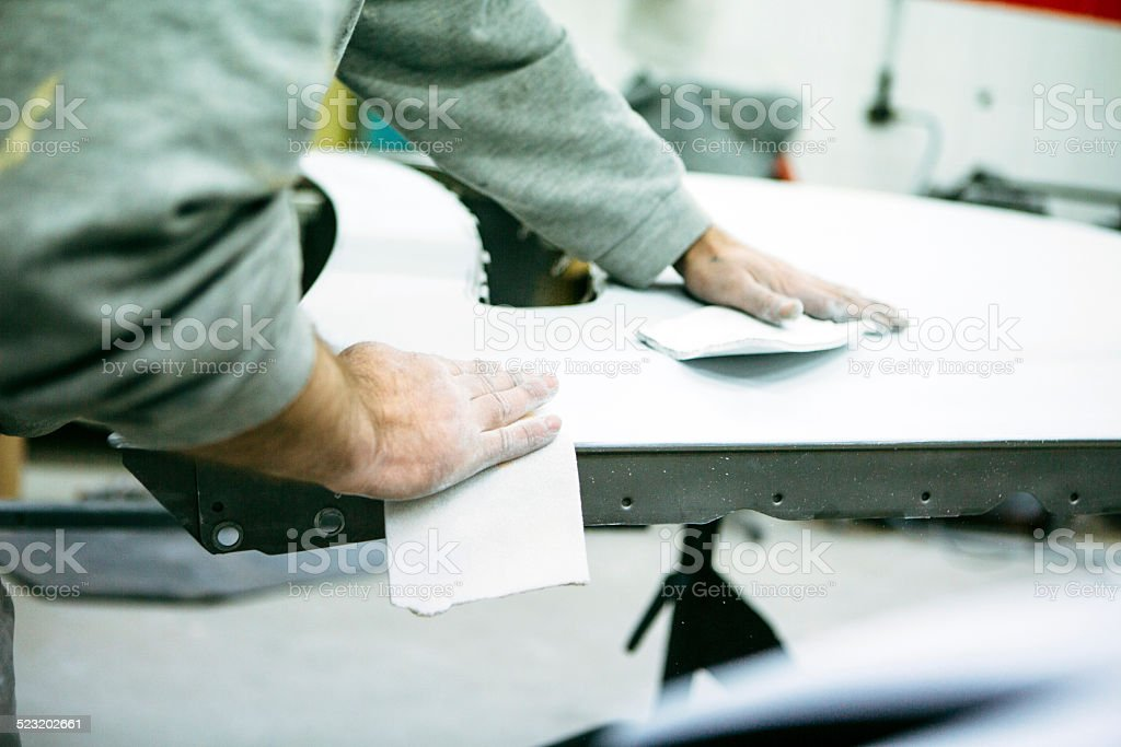 Spray Painter prepares a part of a car for air brush royalty-free stock photo