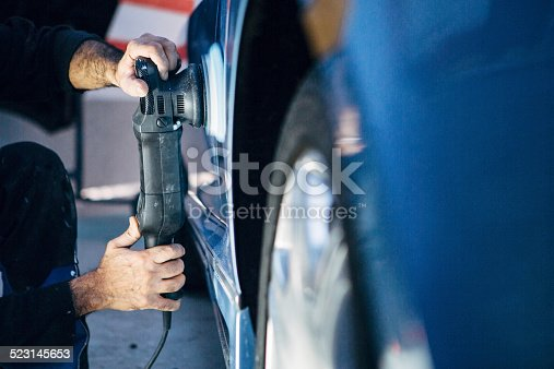 istock Spray Painter works at a car with a polisher 523145653