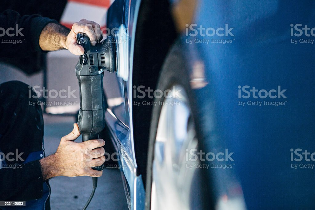 Spray Painter works at a car with a polisher stock photo