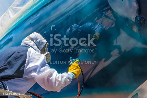 Whangarei, New Zealand, 11-30-2018, worker in full body protection suit and mask is spray painting the hull of a sailing yacht as final work of corrosion protection