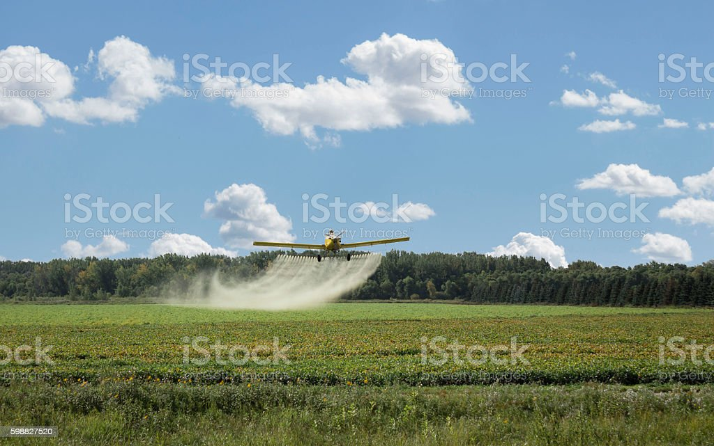 spray plane spraying chemicals on field. stock photo