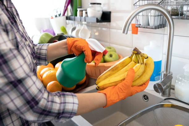 Sprühen antibakterielle Chemikalie auf die Früchte in der Küche. COVID-19 Coronavirus Pandemie Konzept. – Foto