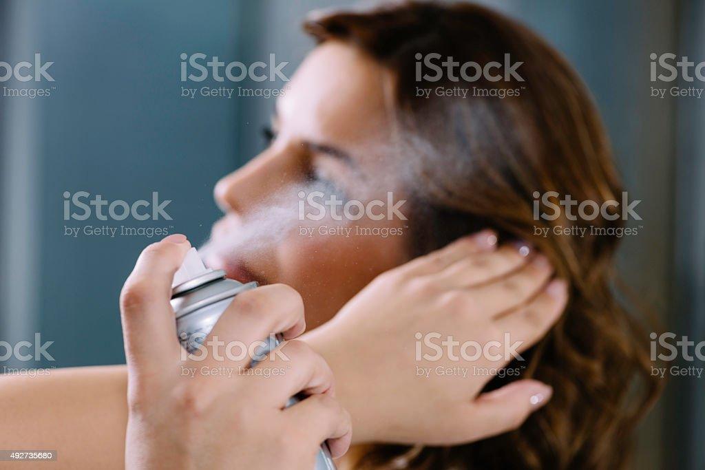 Spraying hair with hair spray in hair salon royalty-free stock photo