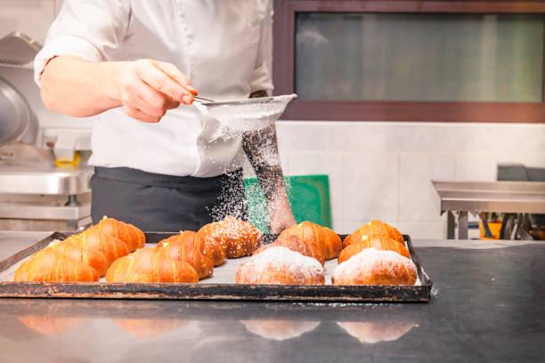 croissants puderzucker aufsprühen - italienische küchen dekor stock-fotos und bilder