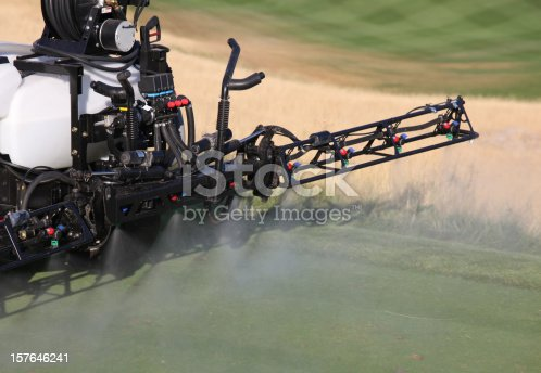 A liquid fertilizer is applied on a golf course. This sprayer is applying a fertilizer or fungicide onto a beautiful golf course. Equipment image with close up perspective on the sprayers. Additional themes include turf management, herbicide, fungicide, agronomy, grass, growing, closeup, nobody, agricultural equipment, spraying, chemicals, environment, poison, treatment, plants, bentgrass, tee box, and pressure.