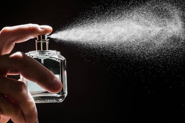 spraying perfume on dark background, closeup  - image - spruzzo profumo foto e immagini stock