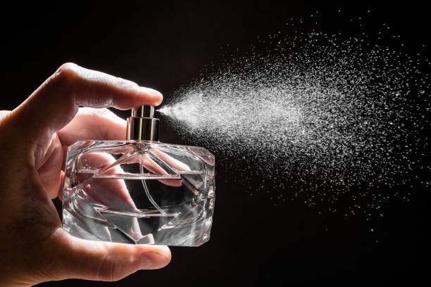 opryskiwanie perfum na ciemnym tle, zbliżenie - zdjęcie - perfumowany zdjęcia i obrazy z banku zdjęć