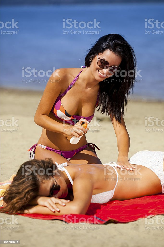 Spraying suntan lotion stock photo