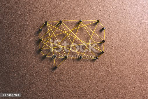 yellow string connecting black pins to make a message bubble.