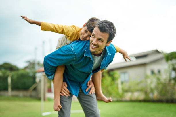 Spread your wings and fly! Shot of a cheerful young father giving his son a piggyback ride outdoors single father stock pictures, royalty-free photos & images