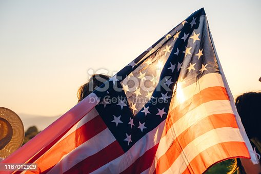 Spreading wide american flag at sunset.