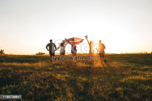 Group of young caucasian handsome people spreading wide american flag at sunset.