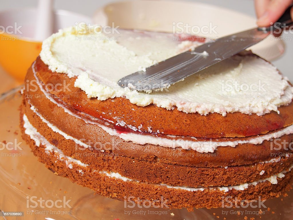 Spreading cake layer with cream stock photo
