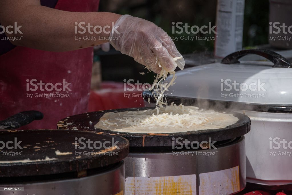 Spreading Cheese over crepes stock photo