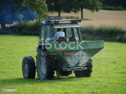 A tractor spreading processed fertilizer