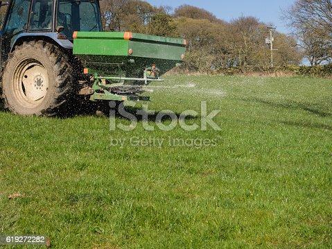 Tractor spreading chemical fertiliser.