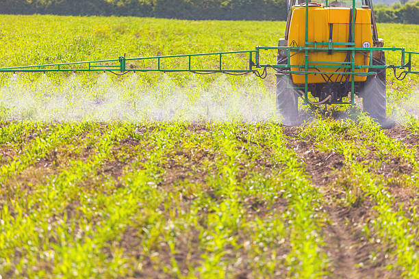 Spreading herbicide A tractor field sprayer spreading herbicide onto field herbicide stock pictures, royalty-free photos & images