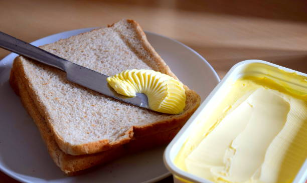 spreading margarine butter onto bread - spargere foto e immagini stock