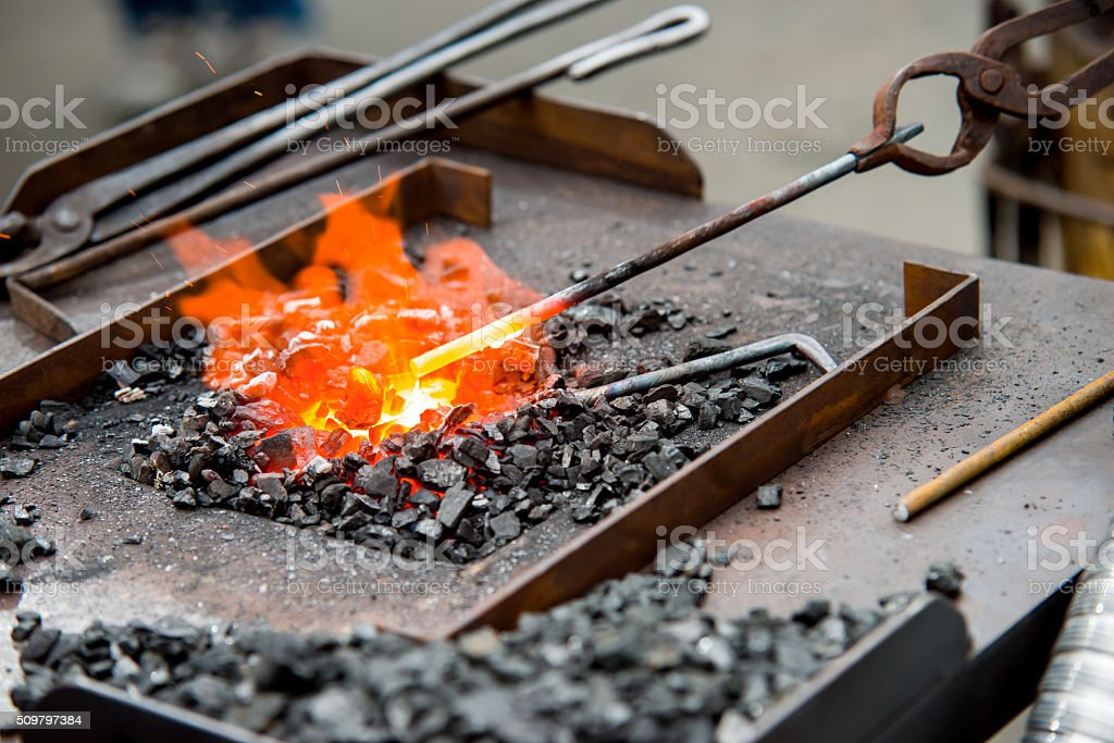 spreading the smith a metal rod in a furnace stock photo