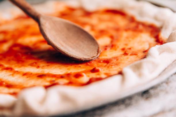spreading tomato sauce on pizza pan - sauce tomatoes imagens e fotografias de stock