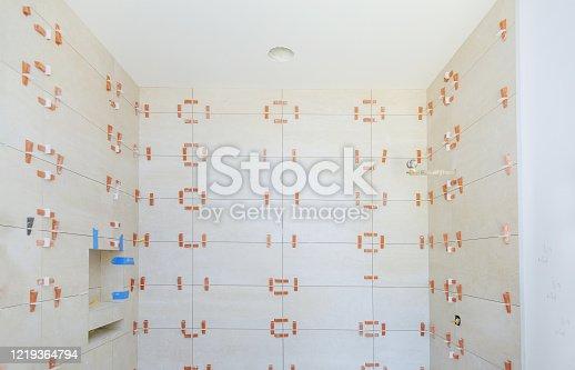 1138442636 istock photo Spreading wet mortar before applying tiles on bathroom tile. 1219364794