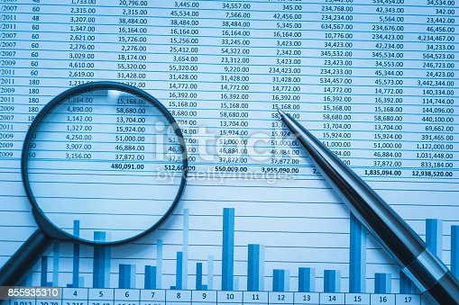 istock Spreadsheet bank accounts accounting finance forensics with magnifying glass and pen. Concept for financial fraud investigation, audit and analysis. 855935310