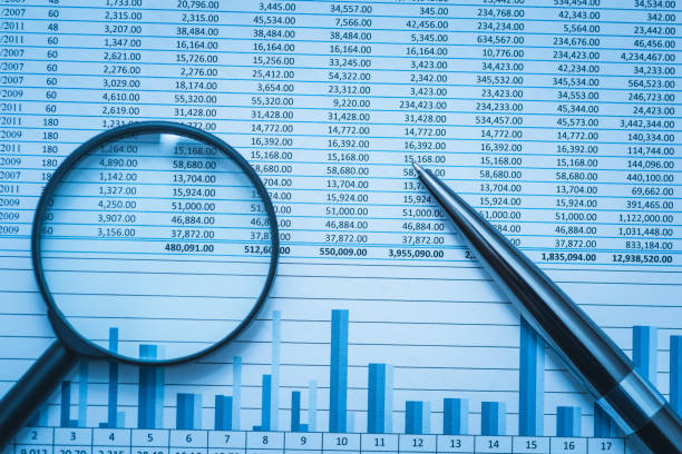 Spreadsheet bank accounts accounting finance forensics with magnifying glass and pen. Concept for financial fraud investigation, audit and analysis. stock photo