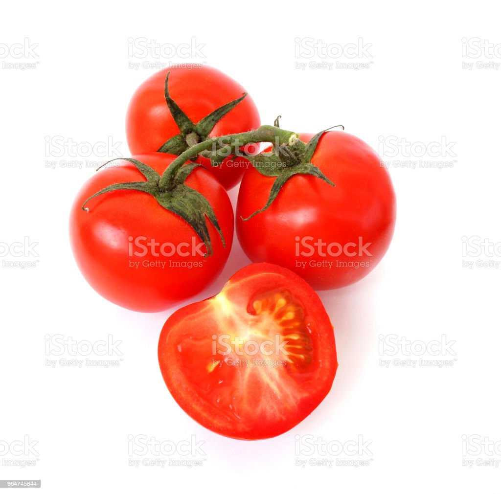 Sprig of ripe tomato on white background. A half of a tomato. Close up. Juicy ripe vegetables. royalty-free stock photo