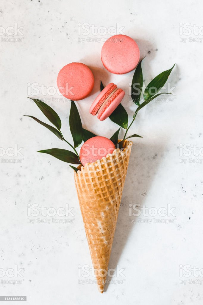 Spring abstract bouquet with a waffle cone, coral macaroons and green...