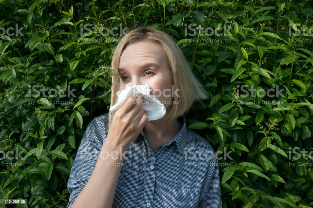 White female, sneezing in front of a green bush