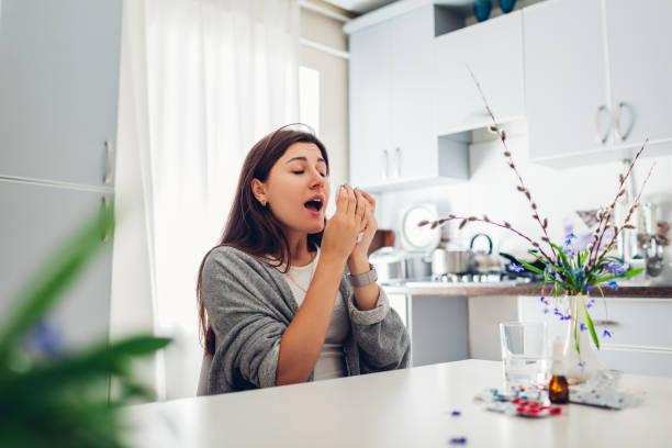 voorjaar allergie. jonge vrouw niezen als gevolg van bloemen omringd met pillen op keuken. seizoensgebonden allergie concept. - allergie stockfoto's en -beelden