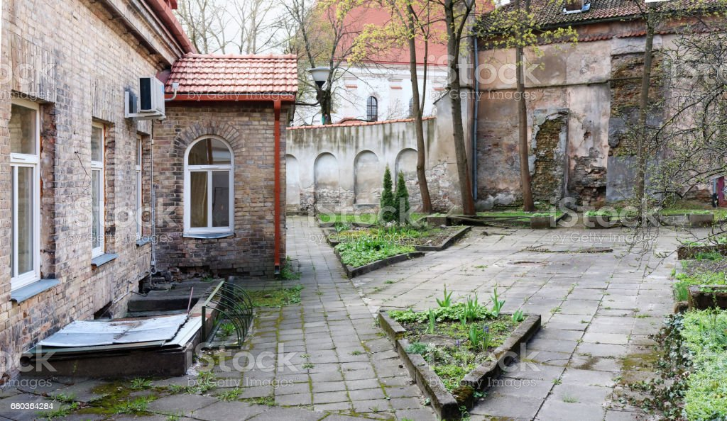 Spring April court yard of the old destroyed  European church. Panoramic urban landscape collage from several outdoor photos royalty-free stock photo