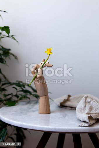 Spring background with copy space, easter daffodils in wooden hand on marble background.
