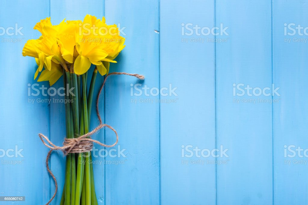 Spring background with daffodils on wooden table stock photo