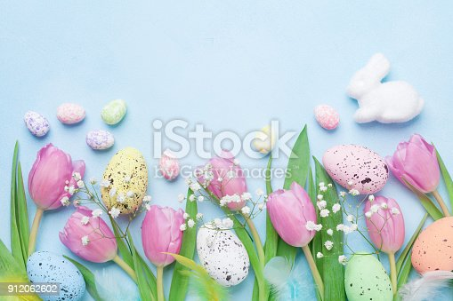 istock Spring background with flowers, bunny, colorful eggs and feathers on blue table top view. Happy Easter card. 912062602