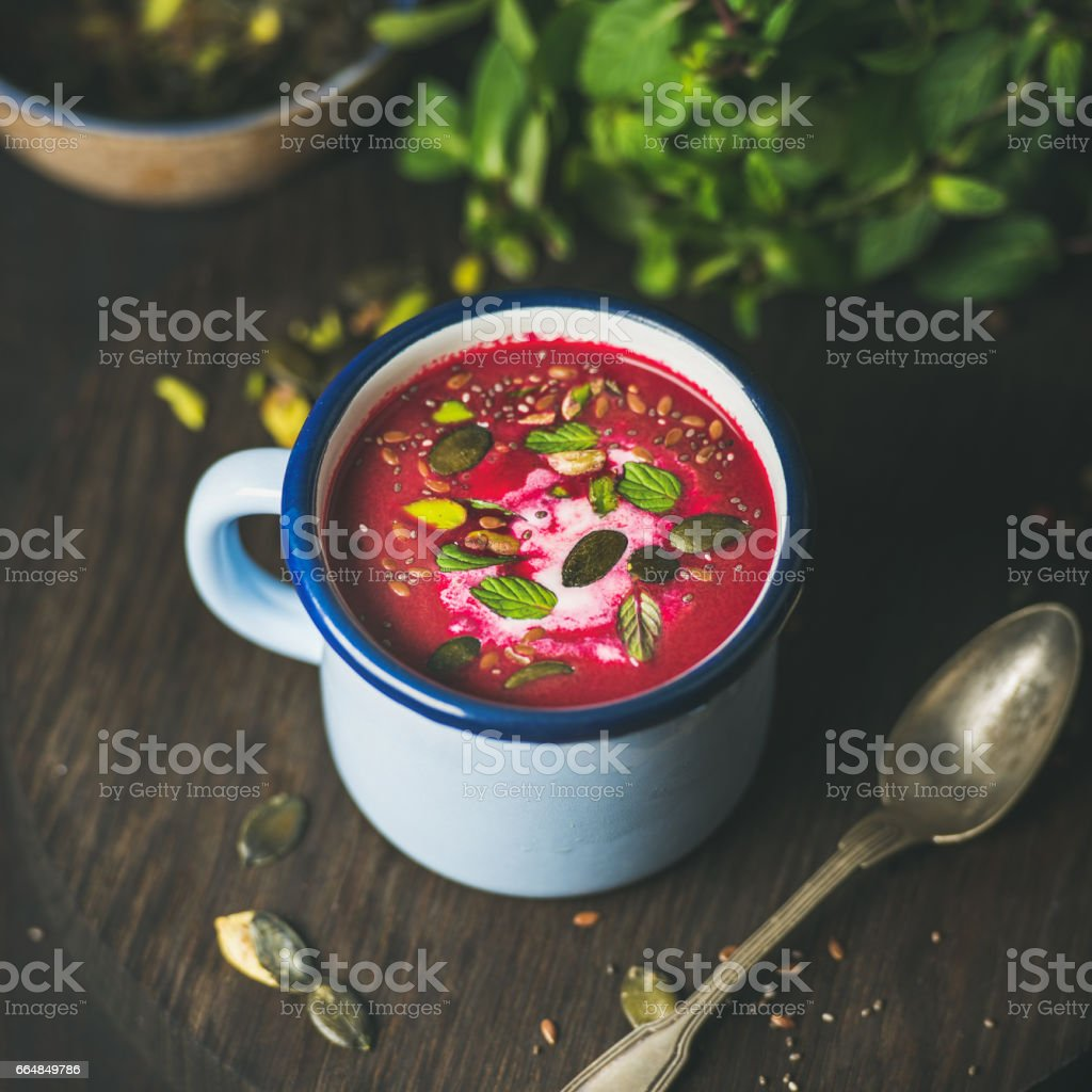Spring beetroot soup with mint, pistachio, chia, flax, pumpkin seeds stock photo